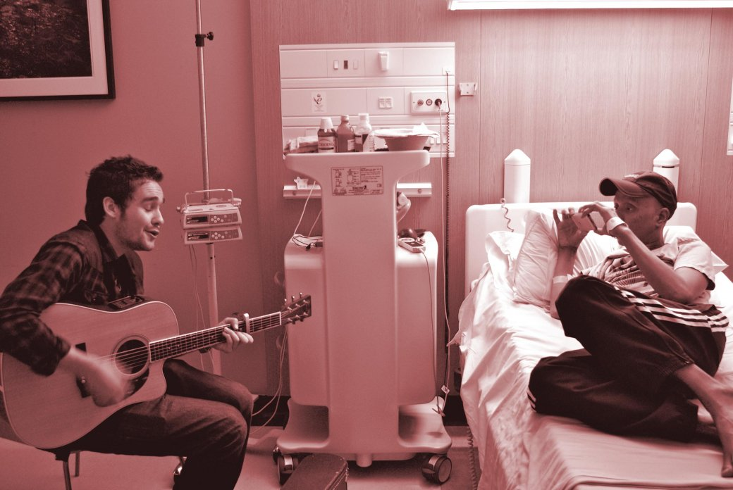 Man playing the guitar in a hospital