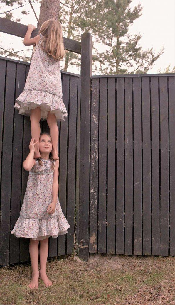 Zwei Mädchen, die sich dabei helfen, über einen Zaun zu schauen